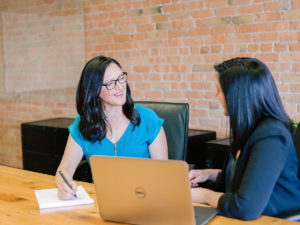 two women talking in a conference room